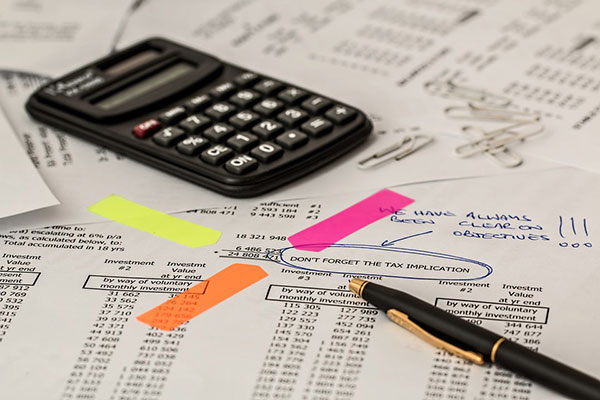 calculator and pen laying on financial documents