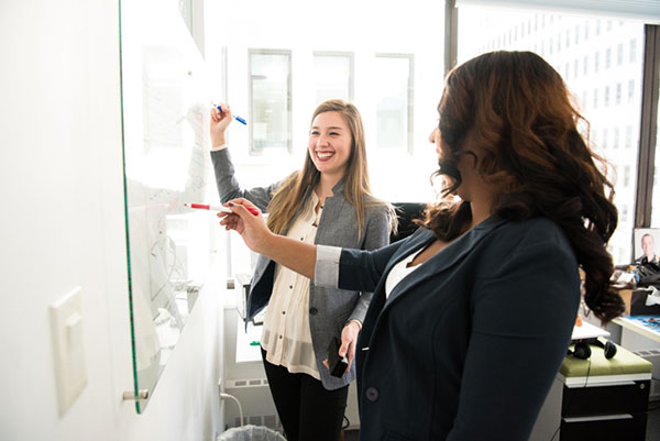 two women in an office writing on a white board